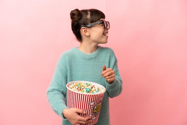 Piccola ragazza caucasica isolata con gli occhiali 3d e che tiene un grande secchio di popcorn