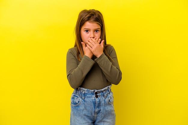 Piccola ragazza caucasica isolata su sfondo giallo che copre la bocca con le mani che sembrano preoccupate.