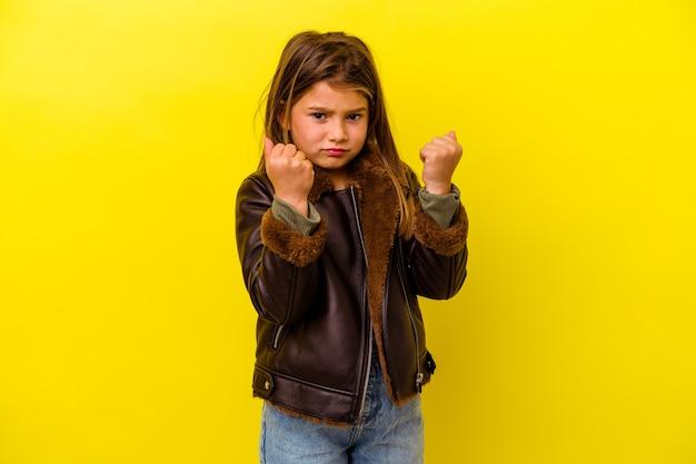 Piccola ragazza caucasica isolata su sfondo giallo che mostra il pugno alla telecamera, espressione facciale aggressiva.