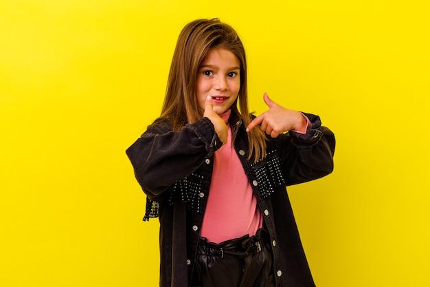 La piccola ragazza caucasica isolata su fondo giallo ha sorpreso indicando con il dito, sorridendo ampiamente.