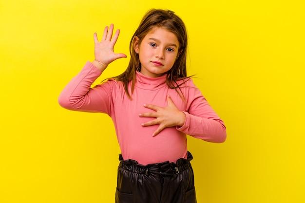 Piccola ragazza caucasica isolata su sfondo giallo prestando giuramento, mettendo la mano sul petto.