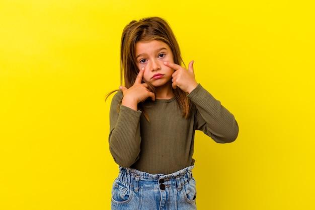 Piccola ragazza caucasica isolata sul pianto giallo, infelice con qualcosa, il concetto di agonia e di confusione.