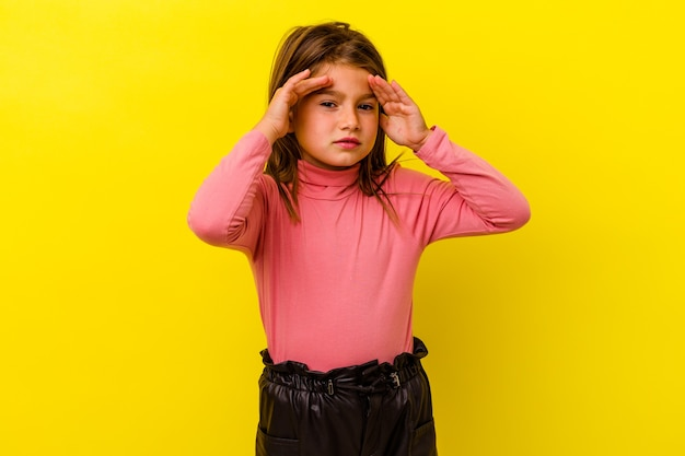 Piccola ragazza caucasica isolata sul muro giallo che copre le orecchie con le dita, stressata e disperata da un ambiente rumoroso.