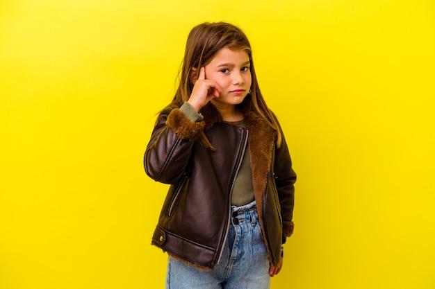 Piccola ragazza caucasica isolata sulle orecchie del rivestimento murale giallo con le mani.