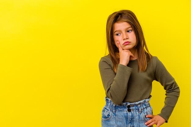 Piccola ragazza caucasica isolata sulla parete gialla che osserva obliquamente con espressione dubbiosa e scettica.