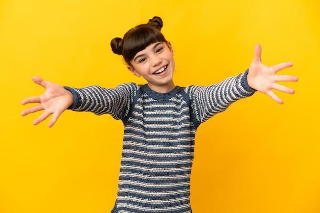 Piccola ragazza caucasica isolata sulla parete gialla che presenta e che invita a venire con la mano