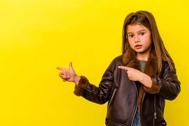 Piccola ragazza caucasica isolata sulla parete gialla scioccata che indica con il dito indice a uno spazio di copia.