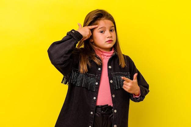 Piccola ragazza caucasica isolata sulla parete gialla che mostra un gesto di delusione con l'indice.