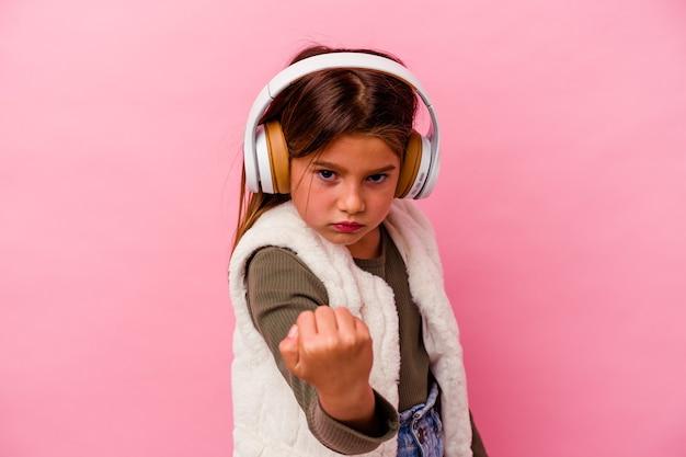 Piccola ragazza caucasica che ascolta musica isolata su sfondo rosa che mostra pugno alla telecamera, espressione facciale aggressiva.