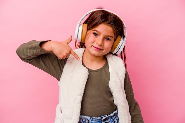 Piccola ragazza caucasica che ascolta musica isolata sulla persona rosa della parete che indica a mano uno spazio della copia della camicia, fiero e sicuro