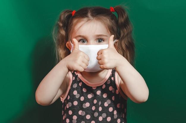 Piccola ragazza caucasica in maschera medica e vestito a pois che mostra il segno del pollice su sfondo verde durante la quarantena e la pandemia di coronavirus 2020
