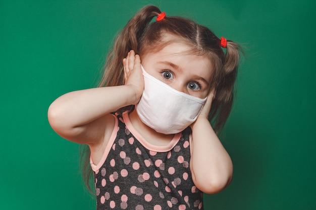 La piccola ragazza caucasica in maschera medica indossa un abito rosso a pois in studio su sfondo verde e tiene la testa nel dolore 2020