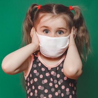 La piccola ragazza caucasica nella mascherina medica indossa un vestito rosso a pois in studio su sfondo verde e tiene la testa nel dolore 2021