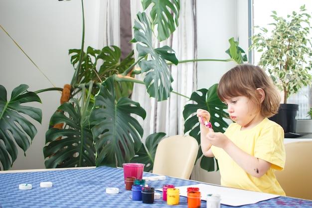 La piccola ragazza caucasica dipinge le piccole figure del giocattolo nell'interno domestico. un bambino di tre anni carino è impegnato nella creatività.