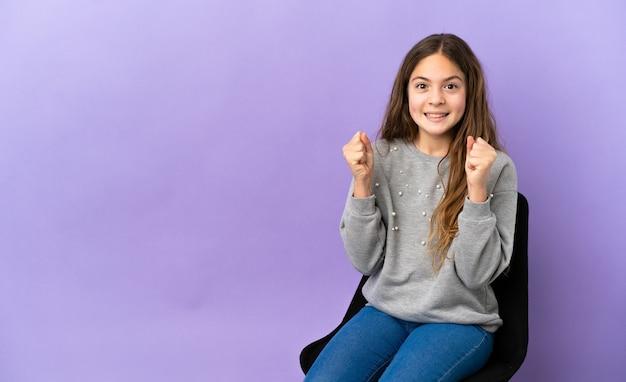 Piccola ragazza caucasica seduta su una sedia isolata su sfondo viola che celebra una vittoria nella posizione del vincitore