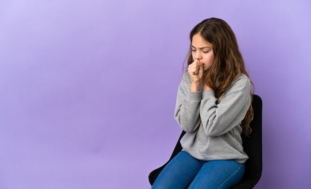 Piccola ragazza caucasica seduta su una sedia isolata su sfondo viola che tossisce molto