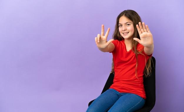 Piccola ragazza caucasica seduta su una sedia isolata su sfondo viola contando otto con le dita