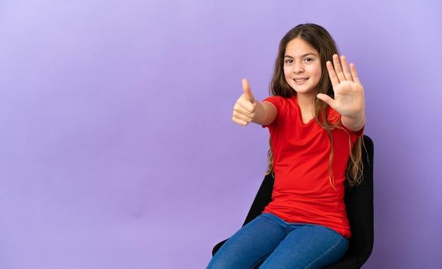 Piccola ragazza caucasica seduta su una sedia isolata su sfondo viola contando sei con le dita