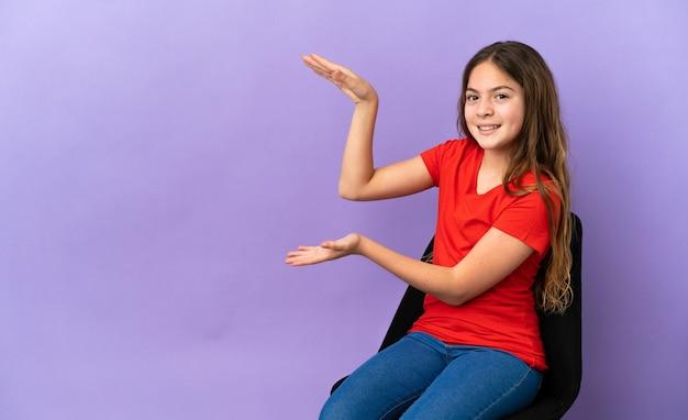 Piccola ragazza caucasica seduta su una sedia isolata su sfondo viola tenendo copyspace per inserire un annuncio