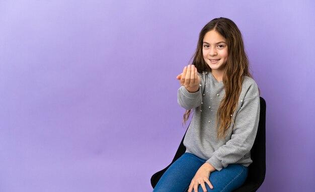 Piccola ragazza caucasica seduta su una sedia isolata su sfondo viola che invita a venire con la mano. felice che tu sia venuto