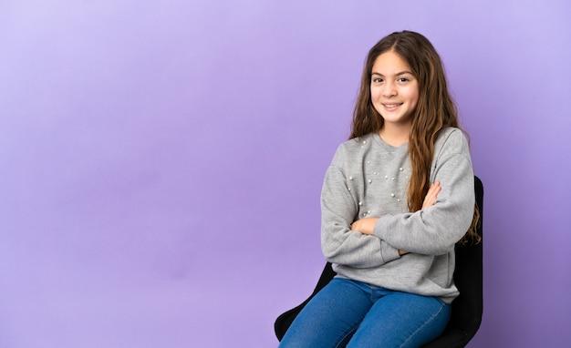 Piccola ragazza caucasica seduta su una sedia isolata su sfondo viola tenendo le braccia incrociate in posizione frontale
