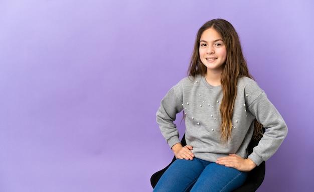 Piccola ragazza caucasica seduta su una sedia isolata su sfondo viola che ride