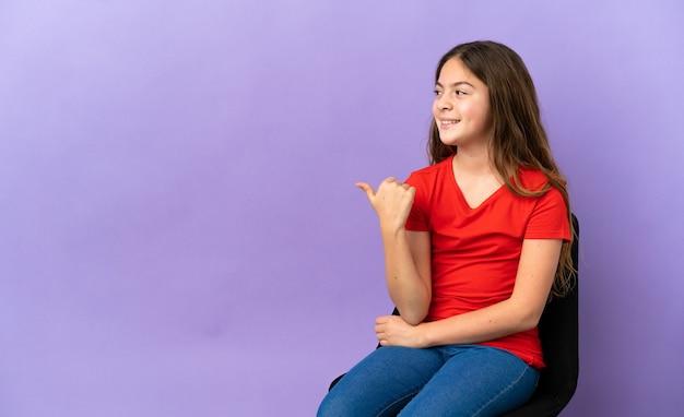 Piccola ragazza caucasica seduta su una sedia isolata su sfondo viola che punta di lato per presentare un prodotto