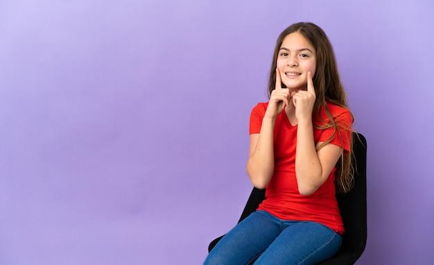 Piccola ragazza caucasica seduta su una sedia isolata su sfondo viola sorridente con un'espressione felice e piacevole