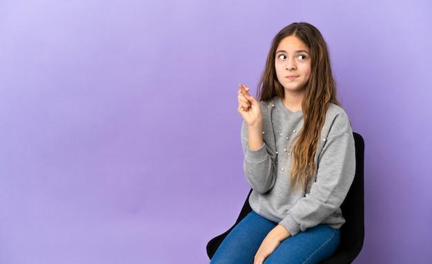 Piccola ragazza caucasica seduta su una sedia isolata su sfondo viola con le dita incrociate e augurando il meglio