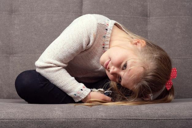 Piccola ragazza caucasica seduta su un divano grigio