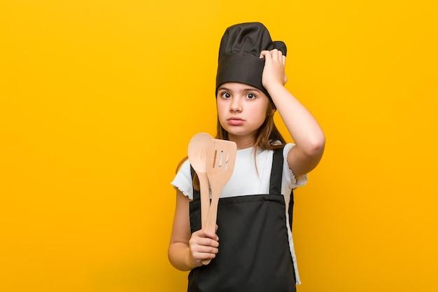 Piccola ragazza caucasica che indossa un costume da chef scioccata, ha ricordato un incontro importante.