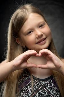 La piccola ragazza caucasica con capelli sciolti biondi mostra un cuore con le sue mani