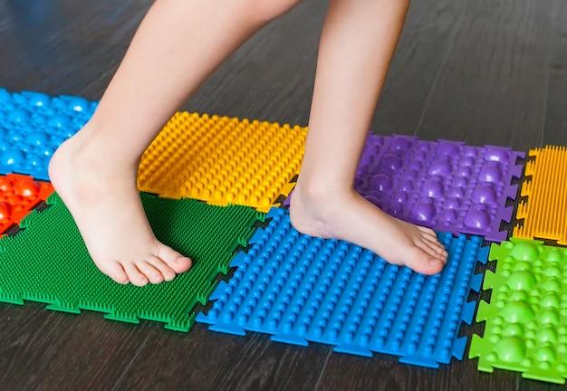 La piccola ragazza sorridente caucasica gioca con i tappetini per bambini con massaggio puzzle con dettagli colorati per prevenire il piede piatto.