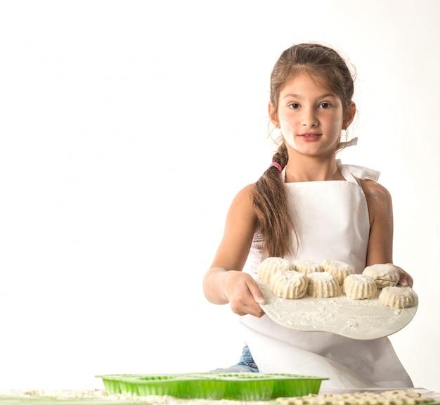 Piccola ragazza affascinante che tiene un bordo con i biscotti