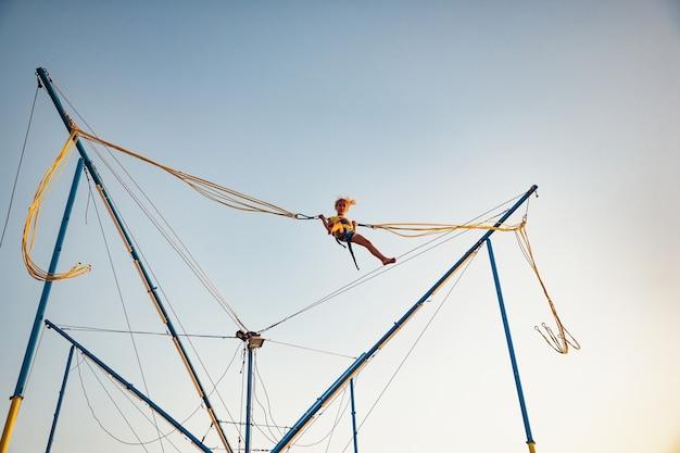 Una bambina allegra vola su elastici elastici luminosi e salta su un trampolino per godersi la tanto attesa vacanza al caldo sole