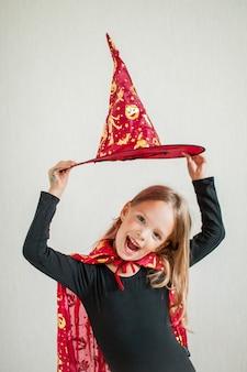La bambina allegra gioca e si diverte in un costume da strega di carnevale
