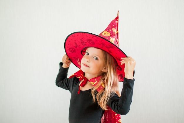 La bambina allegra gioca e si diverte in un costume da strega di carnevale Foto Premium