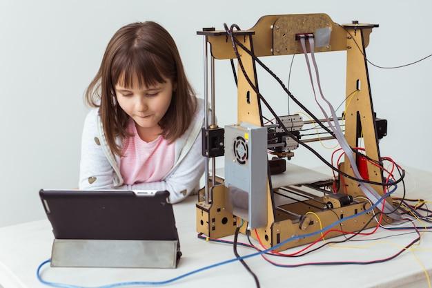Architetto bambino che utilizza la stampante 3d. studentessa, tecnologie e concetto di studio.