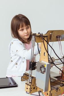 Architetto bambino che utilizza la stampante 3d. studentessa, tecnologie e concetto di studio. Foto Premium