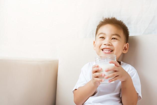 Bicchiere di latte della tenuta della mano del ragazzo del piccolo bambino che beve latte bianco