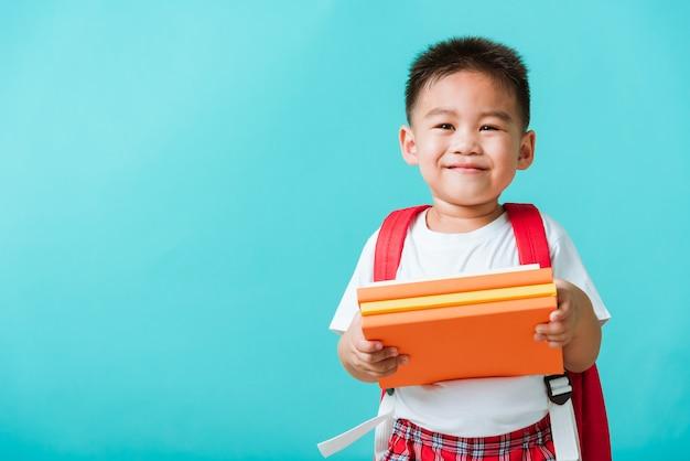 Ragazzino bambino sorridente e ridere in possesso di libri con l'istruzione borsa di scuola