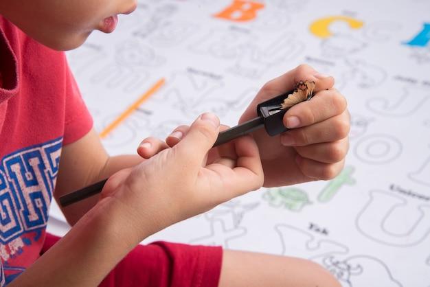 Ragazzo del bambino piccolo utilizzando temperamatite per matita che rade la sua matita colorata
