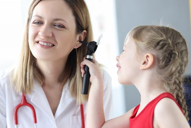 Piccolo bambino che esamina l'orecchio del medico con l'otoscopio in clinica. diagnosi e trattamento delle malattie dell'orecchio nel concetto di bambini