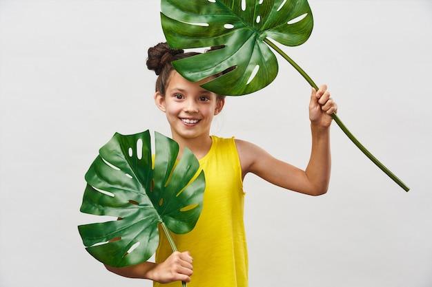Bambina bambino di 9 anni in abito giallo con grandi foglie monstera nelle mani.