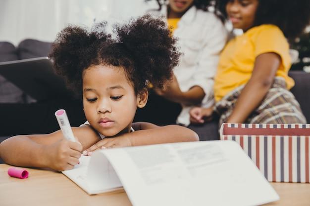 Piccolo bambino ragazza pelle nera che fa i compiti a casa con la sorella e la madre.