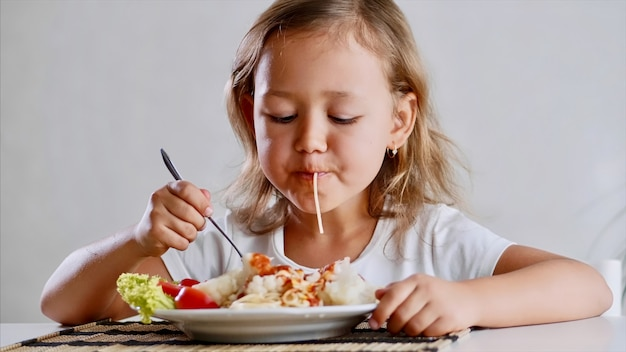 Una bambina piccola sta mangiando gli spaghetti a casa