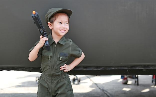 Ragazza del piccolo bambino in costume del vestito del pilota pilota con la pistola della tenuta a disposizione