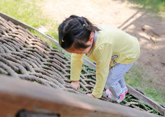 Ragazza del piccolo bambino che gioca sulla rete rampicante