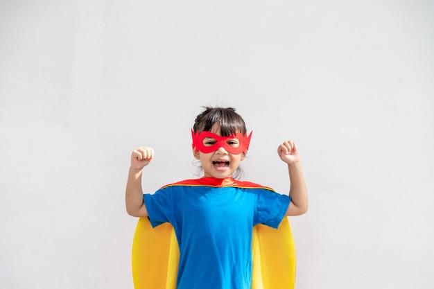 La bambina gioca al supereroe. bambino sullo sfondo bianco. concetto di potere della ragazza