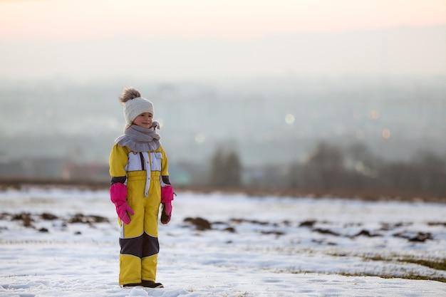 Bambina bambino in piedi da solo all'aperto sul campo invernale innevato.